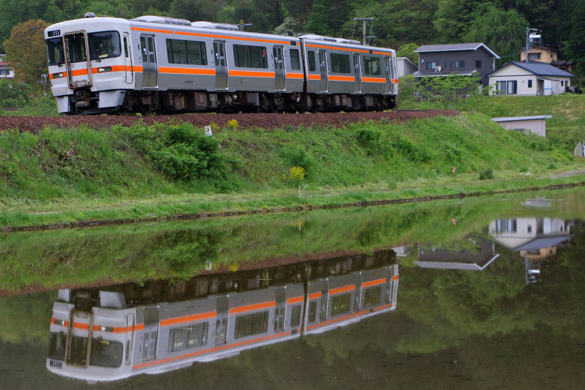 水鏡になった田んぼを走る普通列車